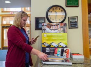 Lady checking out book using mobile checkout in Sioux Center library
