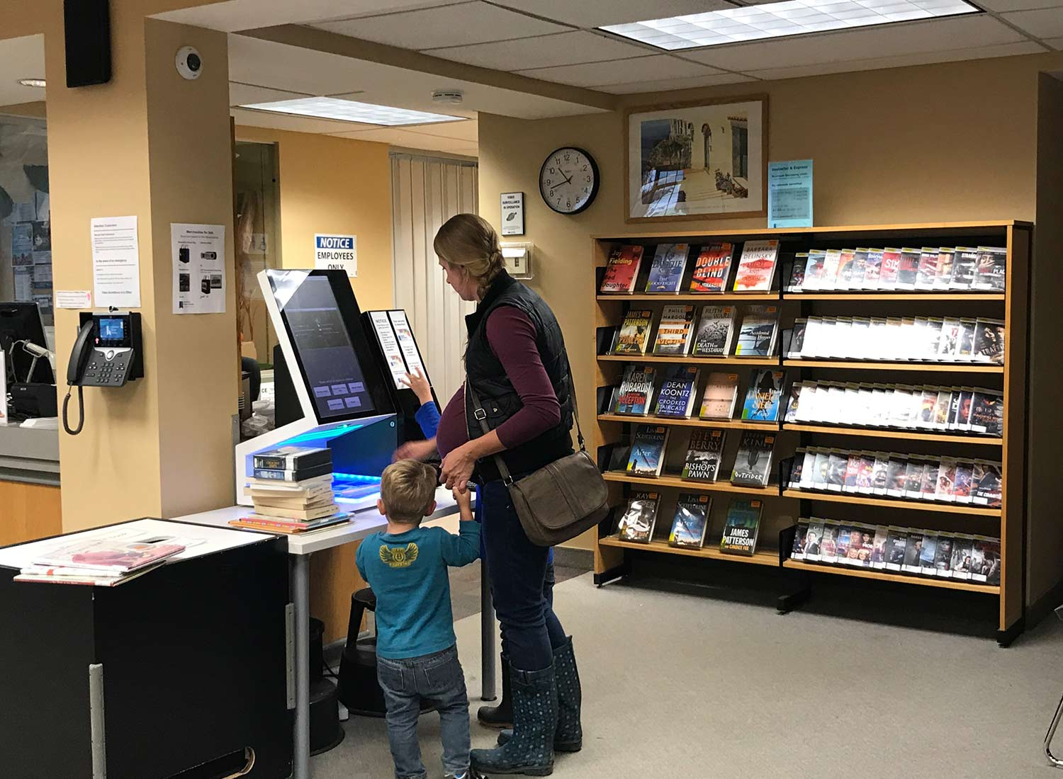 Mother and son checking out books at the selfCheck 1000 in Hamilton library
