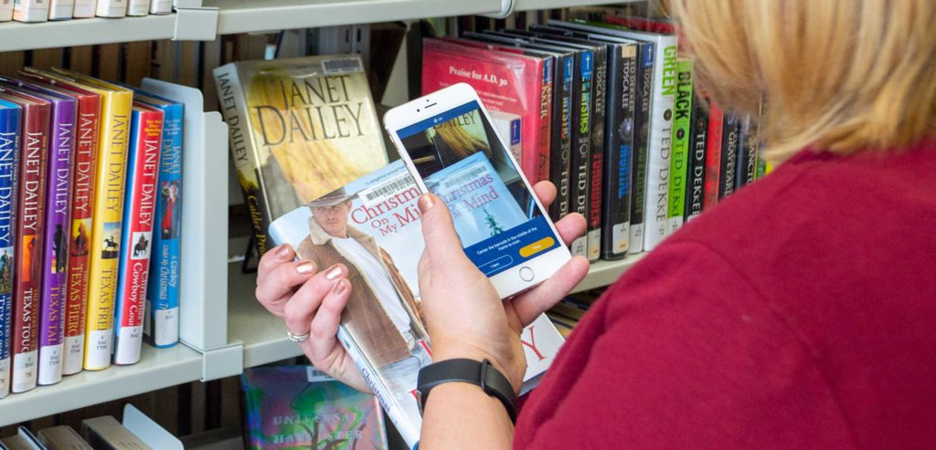 Woman scanning library book barcode with smartphone