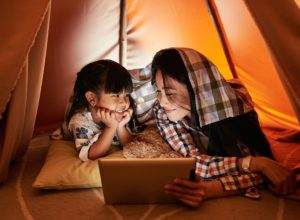 mother and daugther reading of tablet in a den